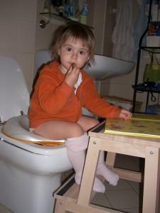 Vera che legge sul wc, a 2 anni